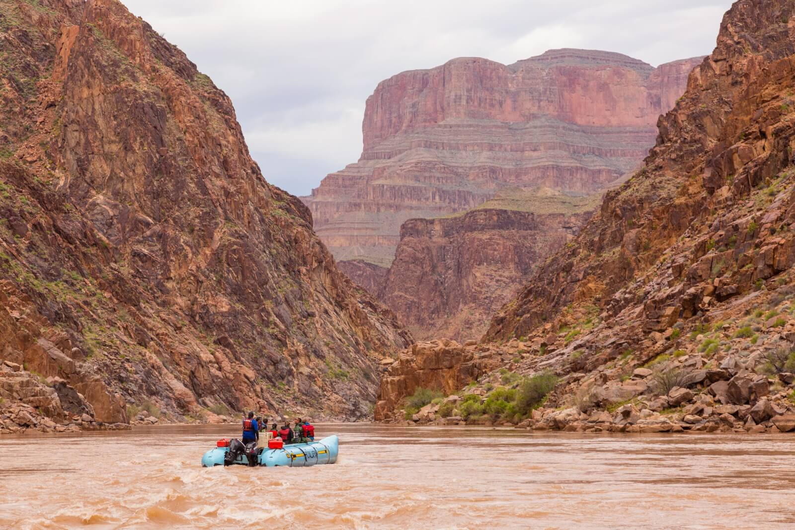A small group of river rafters look at the canyon walls along the Colorado River