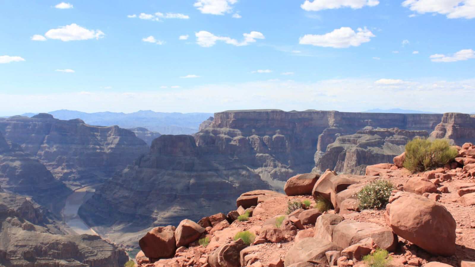 An expansive view of the Grand Canyon West Rim on a clear day with a few puffy white clouds overhead.