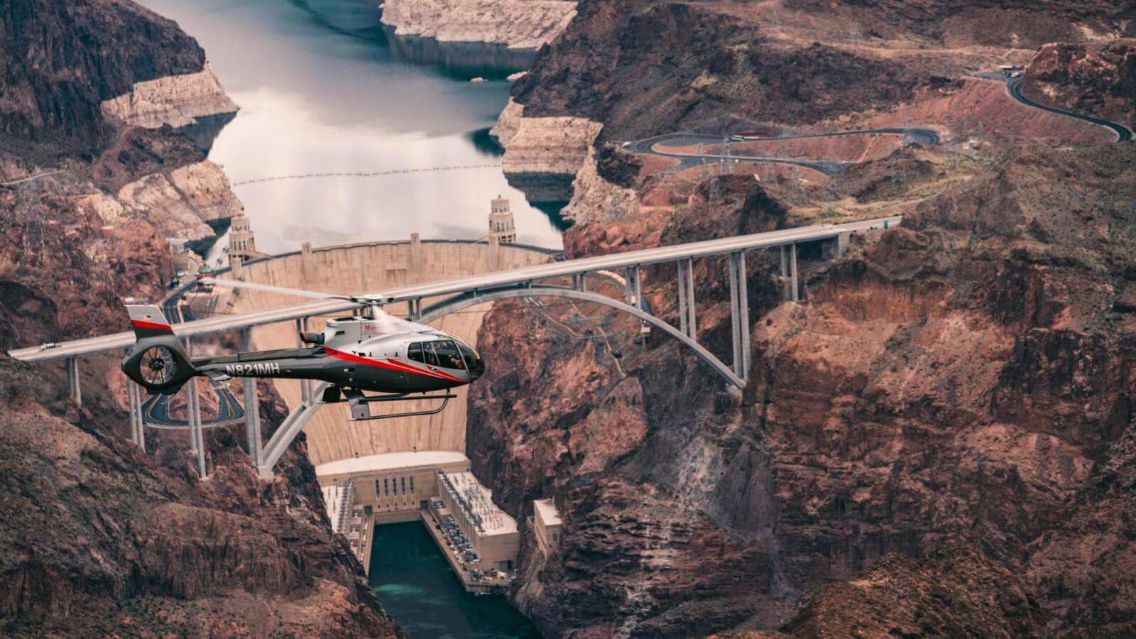 A helicopter soars over the Hoover Dam on its way to the Grand Canyon West.