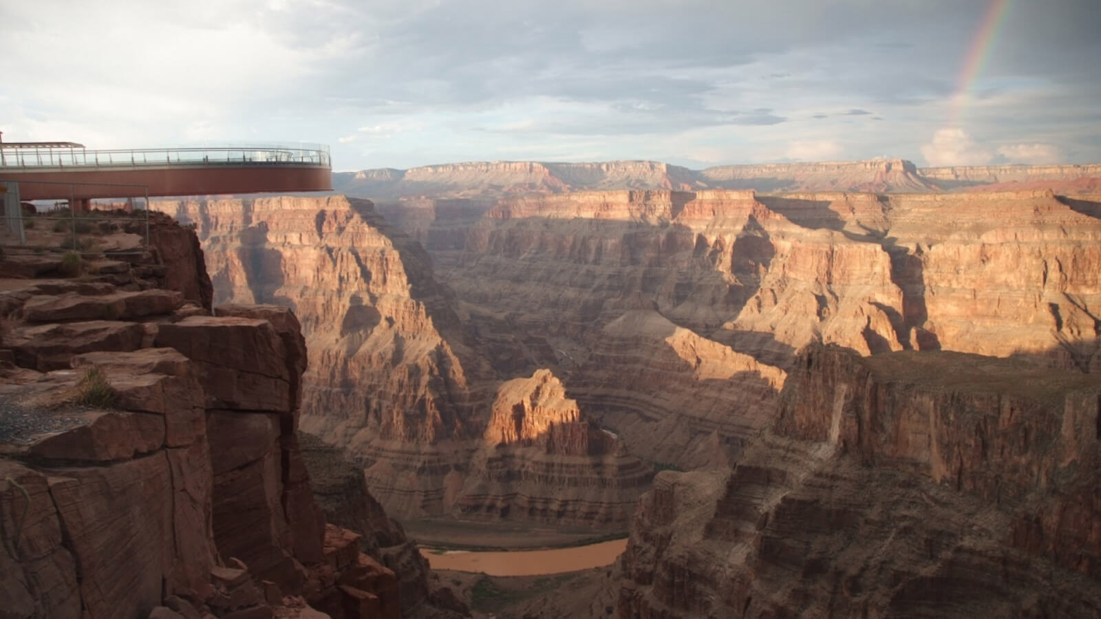 The Skywalk at Grand Canyon West juts out over the canyon with a rainbow in the distance.